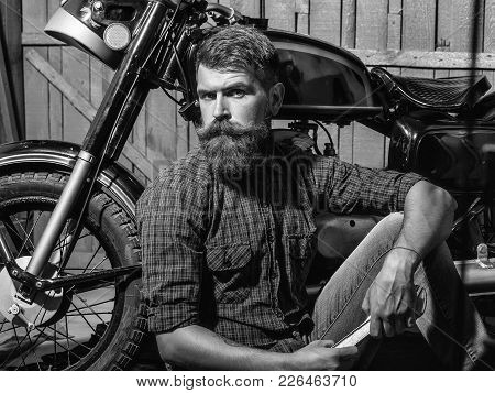 Bearded Man Hipster Biker Brutal Male With Beard And Moustache In Leather Jacket Sits On Floor Near