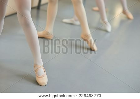 Legs Of Ballerinas In Dance Position. Young Ballet Dancers Performing Dance Move At Class, Cropped I