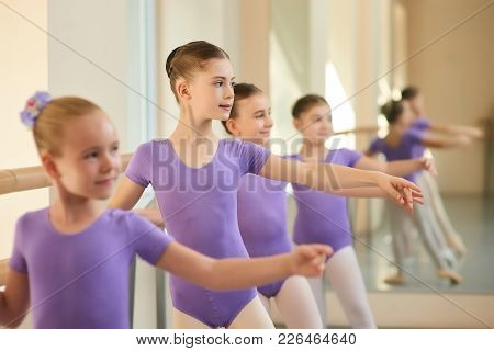 Children In Ballet Dance Class. Beautiful Young Ballerinas In Purple Suits Performing Different Chor
