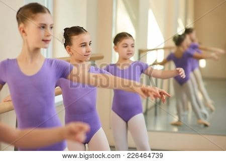 Young Caucasian Ballerinas In Ballet Class. Beautiful Little Ballerinas Training At Ballet Barre In