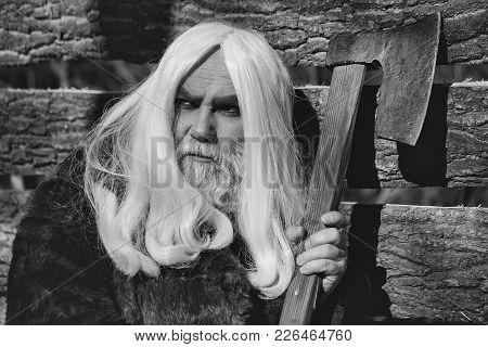 Old Man Druid With Long Silver Hair And Beard In Fur Coat Holding Big Sharp Axe On Wooden House Back