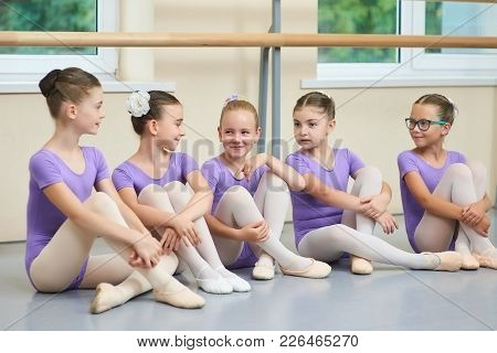 Young Beautiful Ballerinas Talking In Ballet Studio. Group Of Little Ballet Dancers Sitting On The F