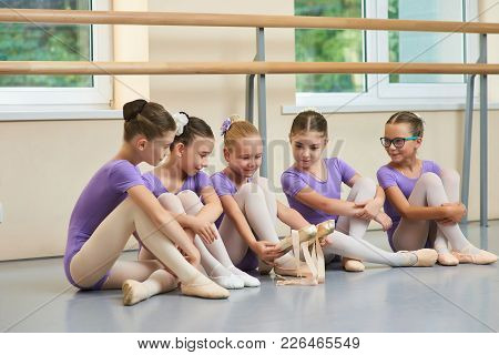 Little Ballerina Showing Her Ballet Shoes To Colleagues. Beautiful Young Ballet Dancer Sitting On Th