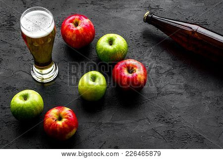 Apple Cider Poured Into Glass Near Bottle And Apples. Black Background Top View.