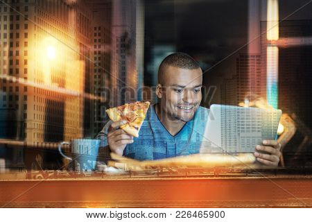 Interested Man. Cheerful Pleasant Handsome Man Looking Interested While Sitting In Front Of A Laptop