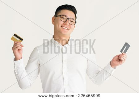 Cheerful Rich Asian Man Enjoying Opportunities With Credit Cards. Happy Excited Young Korean Busines