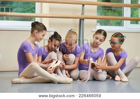 Five Little Ballerinas Sitting On The Floor. Group Of Little Beautiful Ballerinas Resting And Commun