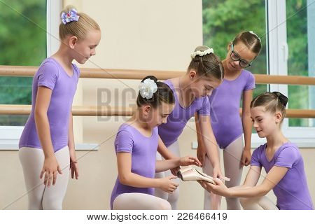 Ballerina Showing Her New Ballet Slippers To Friends. Young Ballerina Giving New Ballet Shoes To Fri