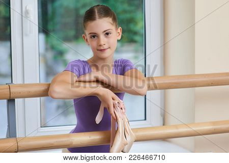 Close Up Portrait Of Little Ballerina. Beautiful Young Ballet Dancer Posing Near Ballet Barre. Adora