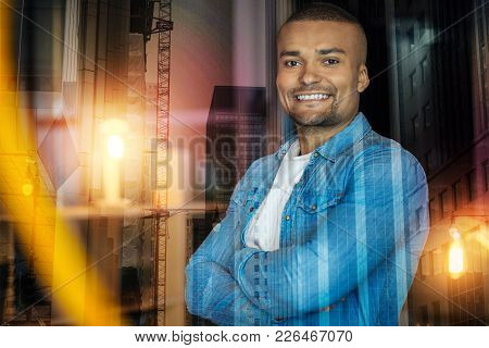 Feeling Happy. Handsome Young Positive Man Feeling Happy While Standing With His Arms Crossed And Fe