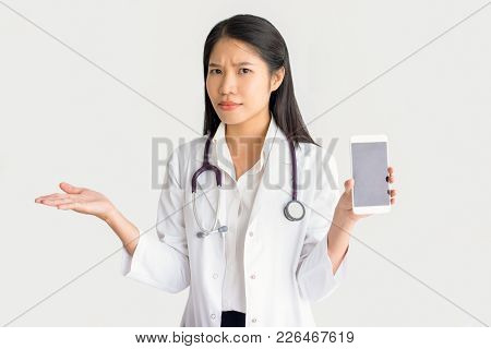 Puzzled Asian General Practitioner With Gadget Shrugging Shoulders And Looking At Camera. Confused F
