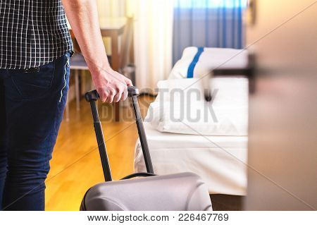 Man Pulling Suitcase And Entering Hotel Room. Traveler Going In To Room Or Walking Inside Motel With