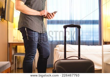 Man Using Smartphone In Hotel Room With Baggage And Suitcase. Tourist With Mobile Phone In Holiday R
