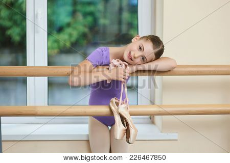 Adorable Little Ballerina With Pointe Shoes. Beautiful Little Ballet Dancer Leaning On Barre At Ball