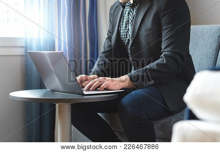 Business Man Working With Laptop In Hotel Room. Businessman Doing Remote Work With Computer. Person