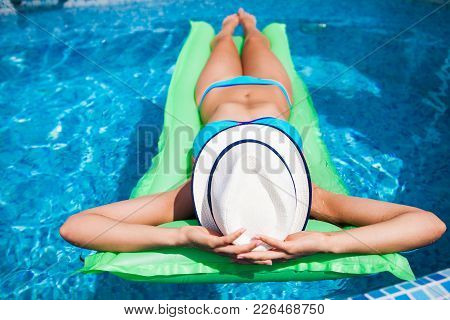 Woman Relaxing On Mattress In The Pool Water In Hot Sunny Day. Summer Holiday Idyllic. Pool Party