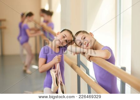 Teen Ballerina In Ballet Class. A Ballet Dancer Resting Her Head On Her Arms At The Barre In A Balle