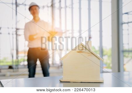 Wooden House Model With Blurred View Of Technician, Architect Or Engineer In Background At Construct