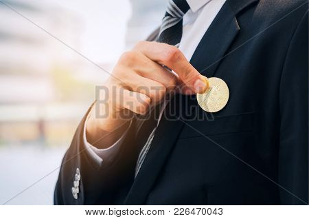 Close Up Hand Of Smart Business Man In Black Suit Pick Bitcoin From Suit Pocket On Modern City Backg