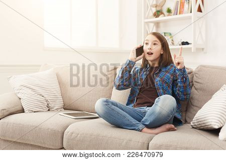Smiling Girl At Home Talking On Mobile, Sitting On Beige Couch In Light Living Room, Heard Something