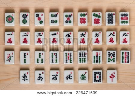 White-green Tiles For Mahjong On A Brown Wooden Background.