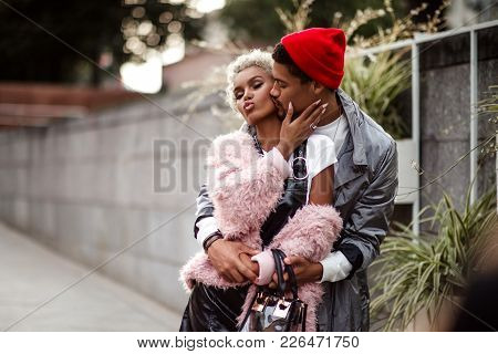 Loving  Couple Embrace Each Other While Have Walk Outdoor, Kiss. Dark Skinned Stylish Male In Trendy
