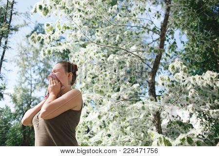 Young Woman Suffering Spring Pollen Allergy. Poplar Bloom Season.