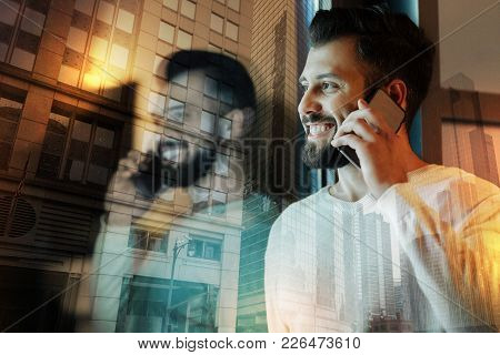 Positive Talk. Cheerful Optimistic Young Man Feeling Pleased While Talking On The Phone And Hearing