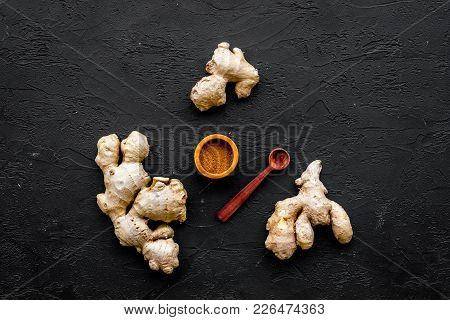 Seasoning. Ground Ginger In Small Bowl Near Sliced Ginger Root On Black Background Top View.