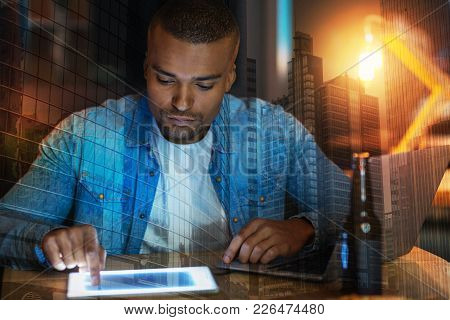 Serious Man. Calm Attentive Young Man Looking Concentrated While Sitting At The Table With A Modern