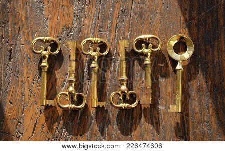 Six Brass Keys On An Old Dark Wood Background