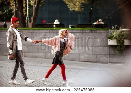 Positive Hipster Guy And His  Girlfriend Hold Hands And Walk Together In Street, Being In Good Mood,