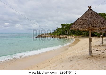 Beautiful Tropical Beach With No People. Reed Beach Umbrellas. Lost Paradise Beach On Island In Anda