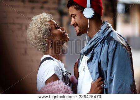 Happy Afro American Man In Heaphones And His Dark Skinned Female With Curly Hairdo Stand Close To Ea