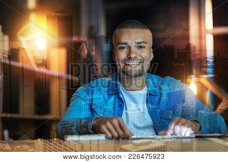 Feeling Glad. Cheerful Emotional Young Person Sitting At The Table With His Fingers Touching His New