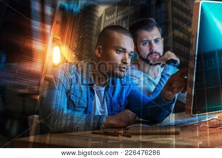 Strange Information. Serious Attentive Young Man Pointing To The Screen Of A Modern Computer And Fee