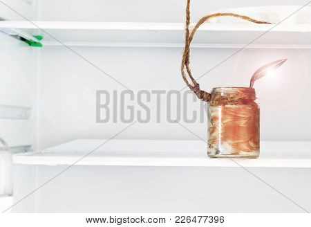 Let The Refrigerator. Rope And An Empty Jar With A Dirty Spoon In A Loop In The Center Of Attention.