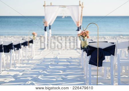 Wedding Ceremony Aisle With Arbor And Chairs On The Beach