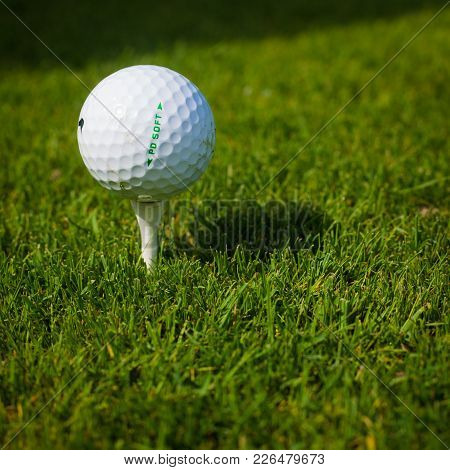 Golf Ball On A Tee Against The Golf Course With Copy Space. Close-up