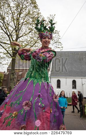 Noordwijkerhout, Netherlands - April 21,  2017: Women In Colorful Dresses Walking On Stilts  At The