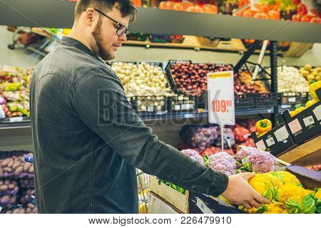 Man Seek Vegetables In Supermarket Stand Near Shelf With Cabbage