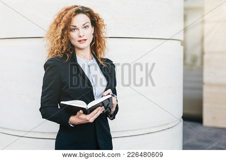 Portrait Of Businesswoman With Curly Hair, Red Painted Lips, Wearing Elegant Clothes, Writing In Her