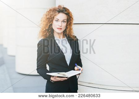Horizontal Portrait Of Serious Pretty Businesswoman With Curly Hair, Thin Eyebrows And Curly Hair, W