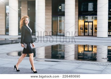 Elegant Slim Woman In Black Suit And High-heeled Shoes, Holding Tablet In Hands Going For Work. Busi