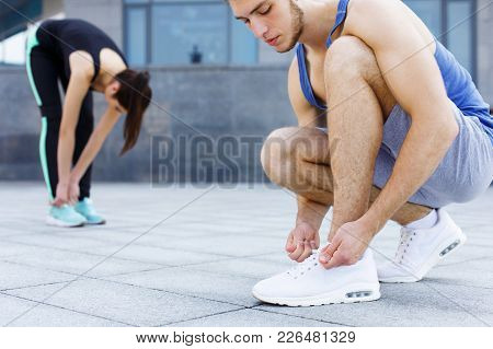 Man And Woman Tying Shoelaces On Sneakers Before Running, Getting Ready For Jogging In City Centre,