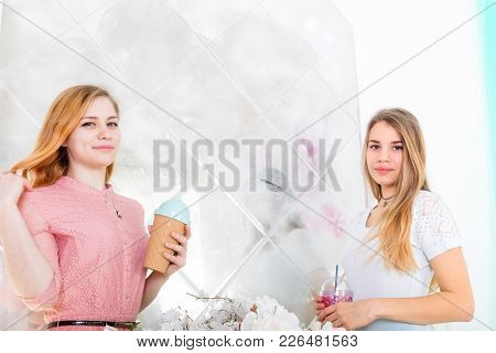 Two Cute Girls In Dresses Drink Drinks From Cups With Lids And Tubes