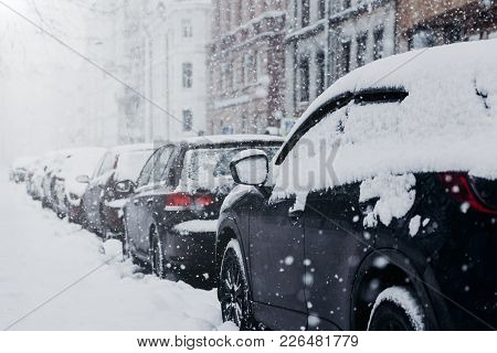 Snow Covered City And Cars. Heavy Snowfall. Much Snow. Cars Parked On Parking Place During Winter We
