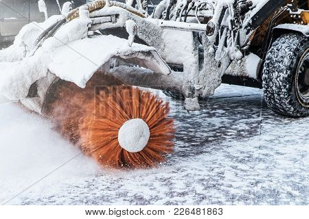 Cleaning Snow Concept. Tractor Clears Way After Heavy Snowfall. Worker Ploughs White Snow After Snow