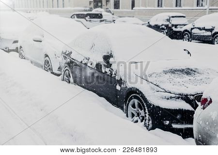 Winter Day In Urban Surrounding. Cars Stand On Parking Lot, Covered With White Snow After Heavy Smow
