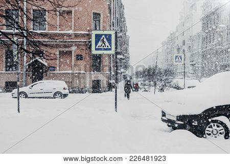 Outdoor Shot Of Beautiful Snowy City With Transport And People, Covered With Thick White Snow During